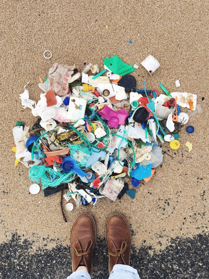 Beach combing trash - turning the findings into beautiful flat lay artwork. Collection of plastics off beach. Colored plastic collected to make photography artwork.