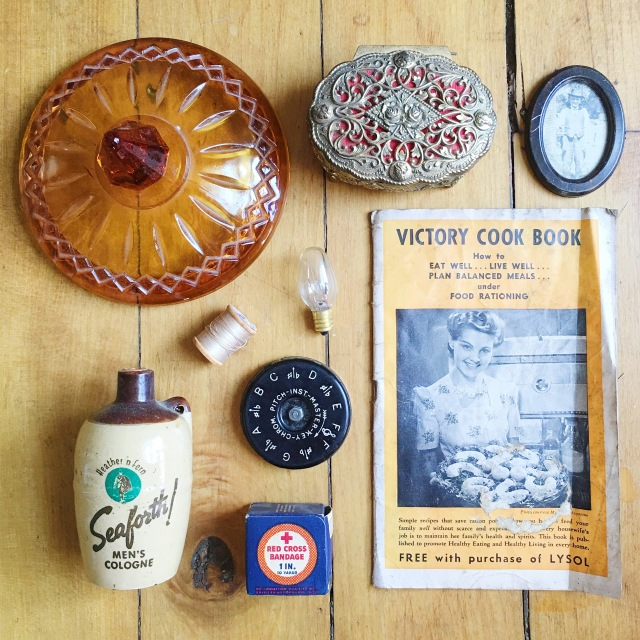 Flat lay of found objects in Virginia Farm House. Vintage items, Seaforth Mens Cologne, Red Cross Bandage, Victory Cook Book, Vintage photos and objects