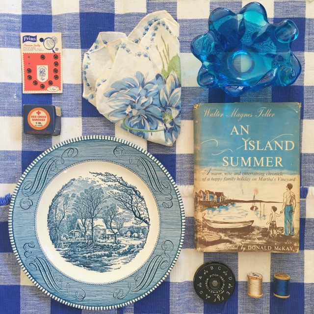 Flat lay of found objects in Virginia Farm House. Vintage items, glass candle holder, blue china plate, handkerchief, Donald Mckay novel - An island Summer. Buttons, Thread and blue gingham napkins