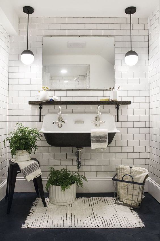 White subway tiles - hanging lights, white tile bathroom, black floors. Schoolhouse sink. Bathroom with plants