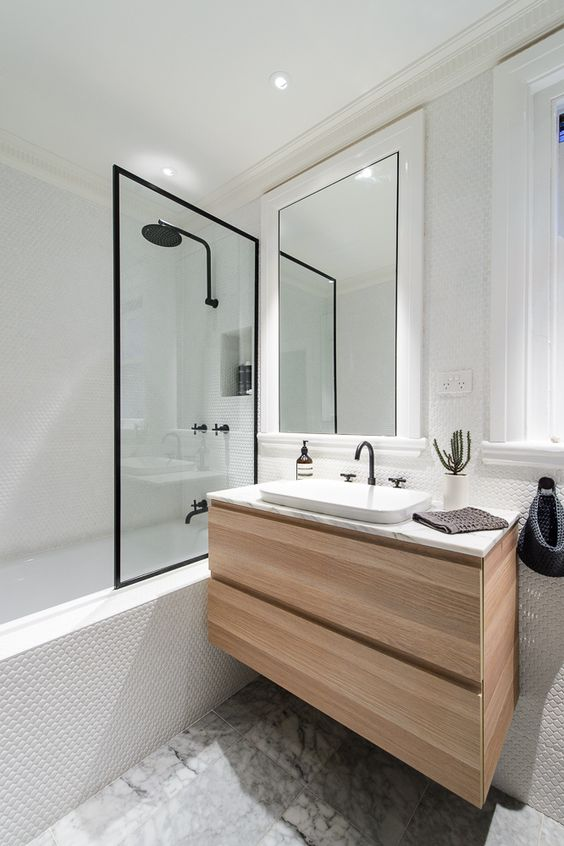 Bathroom with light wood and black trim. Black trim mirror. White tile bathroom with clear glass. Marble Bathroom with white and black
