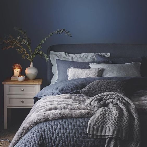 Bedroom with blue accents, neutral linens and fantastic wall sconce features. Modern Side Tables and interesting artwork